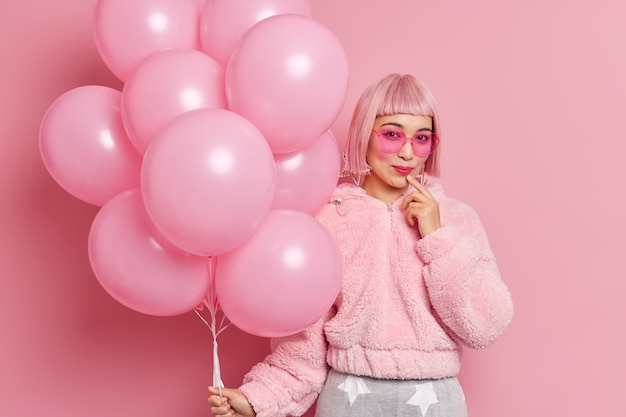 Good looking stylish asian woman wears pink wig with fringe trendy sunglasses fur coat holds bunch of helium balloons ready for hens party poses indoor