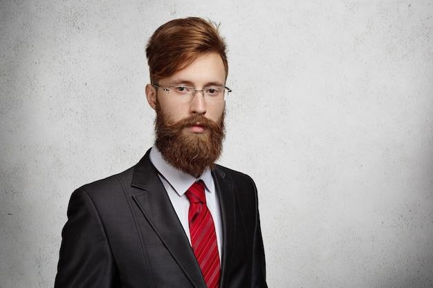 テキストまたはプロモーションコンテンツのコピースペースを持つ灰色の壁に対して隔離されたポーズの厚いひげと長方形のメガネで格好良いスタイリッシュな赤毛の起業家またはオフィスワーカー