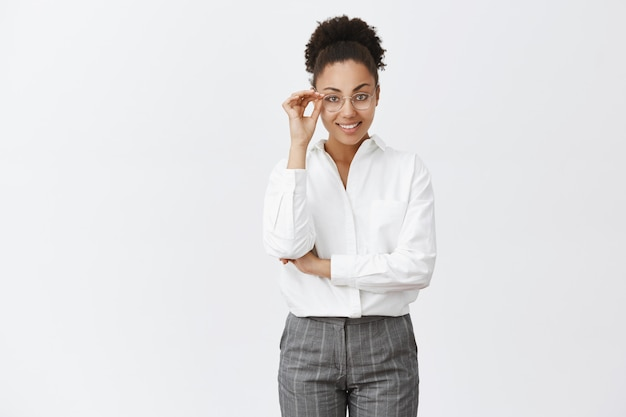 Good-looking stylish and smart female psychologist with dark skin in white-collar shirt and pants, touching glasses and smiling with self-assured expression, gazing