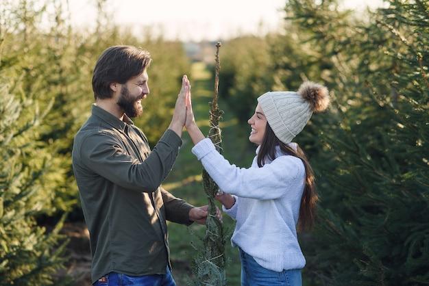 Симпатичная стильная улыбающаяся молодая пара завязывает нитками красивую елку и дает пять.