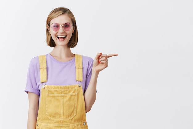Good-looking stylish young woman in sunglasses smiling, recommend promo, pointing finger right