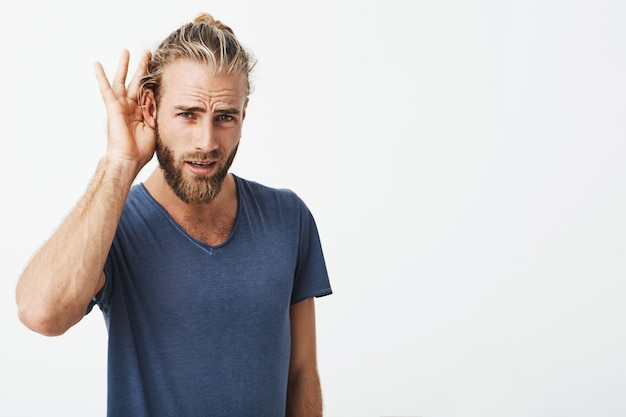 Good-looking swedish guy with beard and cool hairstyle holding hand near ear