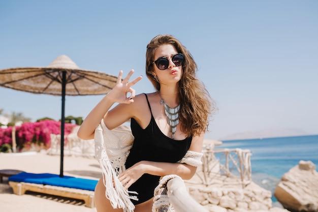 夏の朝、海のビーチで休憩しながらポーズをとる美しい顔の日焼け少女。海の前のリゾートで楽しんでネックレスを持つ素晴らしいブルネットの女性