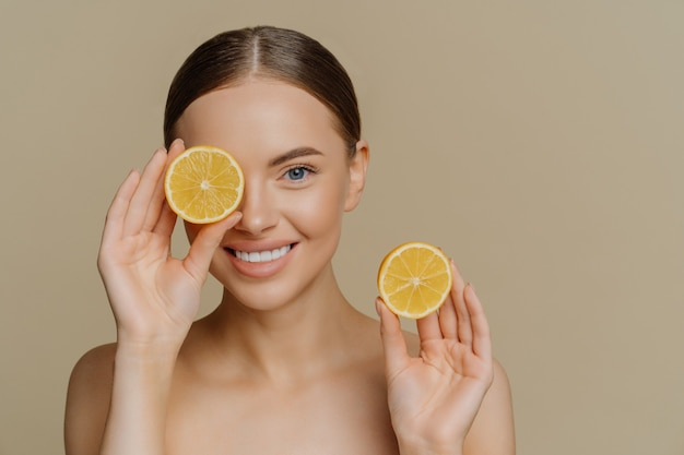 Good looking tender brunette woman smiles gently, covers eye with half of orange holds favorite fruit poses topless indoor