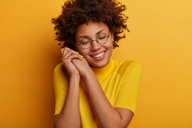 Good looking tender young female model leans at hands, smiles tenderly, closes eyes and imagines something wonderful or pleasant, being touched, wears spectacles and yellow outfit, has romantic mood