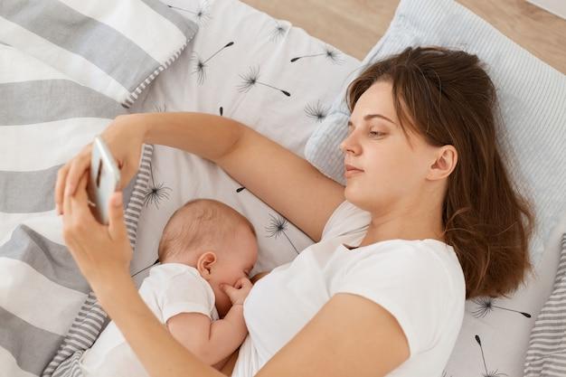 침대에 누워 아기에게 모유 수유를 하는 동안 휴대폰을 사용하여 네트워크를 확인하거나 메시지를 입력하기 위해 흰색 캐주얼 스타일의 티셔츠를 입은 잘 생긴 피곤한 졸린 여성.