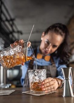 Good-looking waitress focuses on pouring old fashioned whiskey cocktail into an ornamental glass in a pub.