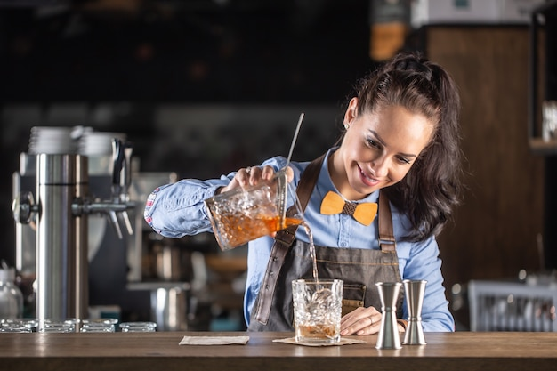 Good-looking waitress pours old fashioned whiskey cocktail into an ornamental glass in a pub.