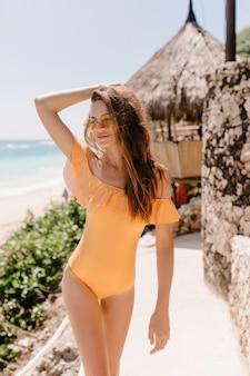 방갈로 앞에 서있는 잘 생긴 백인 여성 모델. 바다 리조트에서 태양을 즐기는 오렌지 수영복에 매혹적인 무두 질된 여자의 야외 사진.