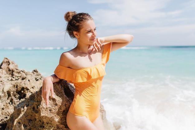 Красивая белая девушка в ретро купальниках, глядя в сторону. модная шатенка в желтой одежде, стоя на берегу океана и трогательно скале.