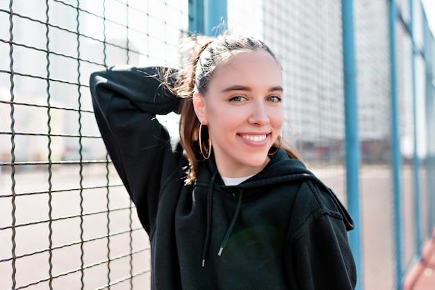 Красивая женщина, одетая в черный пуловер и позирует на детской площадке в солнечном свете