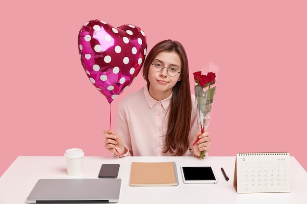 Good looking woman has attentive look , recieves pleasant presents from boyfriend at office, holds valentine balloon and roses, wears spectacles