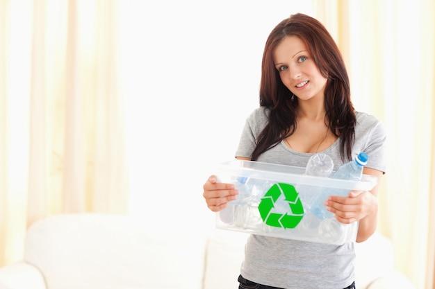 Good looking woman holding recycling bin