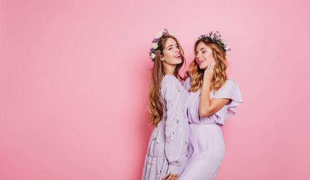 Красивая женщина в цветочном венке улыбается на розовой стене