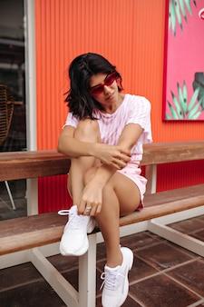 木製のベンチに座っている白いスニーカーの格好良い女性。夏の装いで洗練されたヨーロッパの女性の屋外ショット。