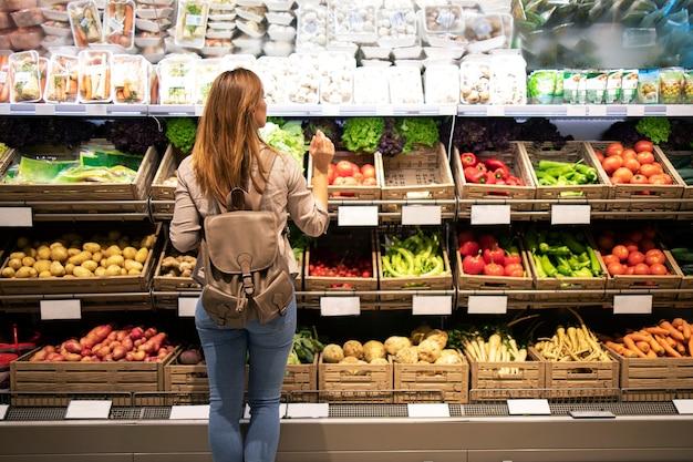 Красивая женщина стоит перед овощными полками и выбирает, что купить