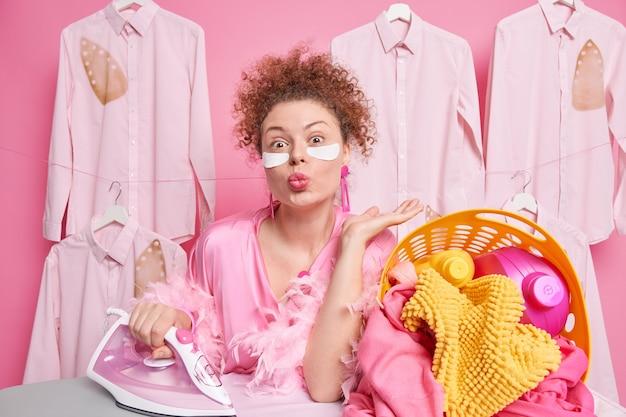 Красивая женщина с вьющимися причесанными волосами держит губы округлыми, хочет поцеловать вас, занятую домашними делами, одетая в домашнюю одежду, стоит возле корзины с гладильной доской, полной белья и моющих средств