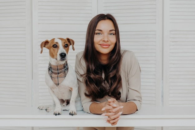 Good looking woman with dark hair, spends leisure time with jack russel terrier dog