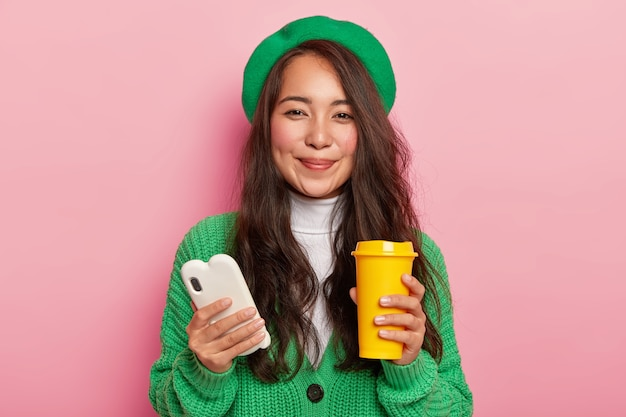 Good looking woman with dark straight hair, rouge cheeks holds white mobile phone and coffee cup, enjoys free time for surfing social networks