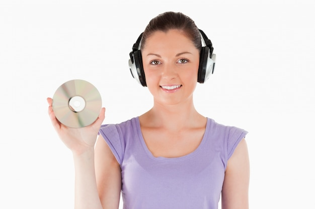 Good looking woman with headphones holding a cd while standing