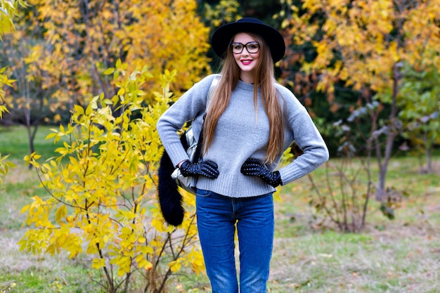 Good-looking woman with long hair wears jeans and gloves standing in confident pose on nature background. outdoor photo of pretty female model in trendy gray sweater walking in park in autumn day.