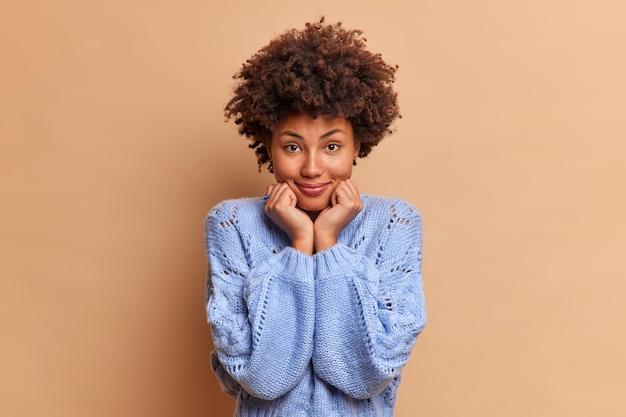 自然な巻き毛の格好良い女性は、青いジャンパーを着たあごの下に手を保ち、正面のスタンドを直接見て自信を持って、茶色の壁に対して美しいスタンド