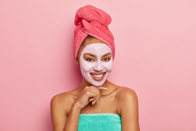 Good looking woman with pleased expression, touches chin gently, wears cleansing clay mask on face, has wrapped towel on head, enjoys beauty treatments at home, isolated on pink wall
