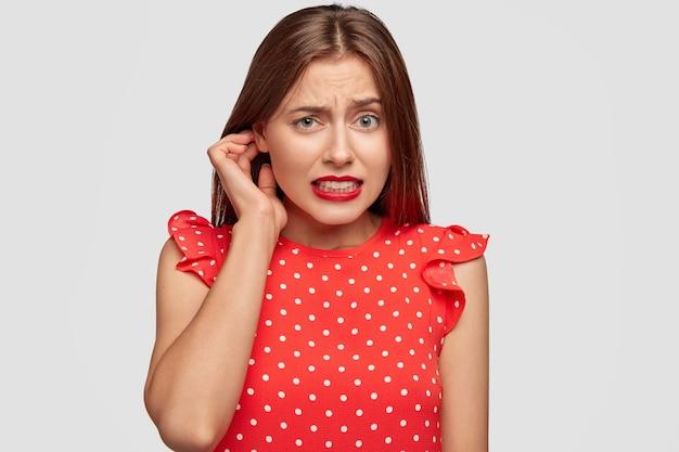 Bella donna con rossetto rosso in posa contro il muro bianco