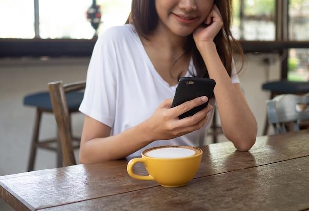 格好良い女性はスマートフォンを使ってインターネットに接続し、外国人の友達とコミュニケーションやチャットをしています。幸せでリラックスした女性がカフェに座っています。働く女性とフリーランスのコンセプト