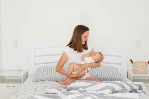 잘 생긴 젊은 성인 어머니는 침대에 앉아 있는 동안 매력적인 작은 아기와 함께 포즈를 취하고, 어린 아이를 바라보고, 집의 밝은 방에서 포즈를 취하는 가족을 바라보고 있습니다.