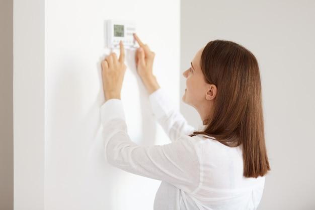 흰색 캐주얼 스타일의 셔츠를 입은 잘 생긴 젊은 성인 여성, 벽에 연결된 가전 제품, 에너지 보안 난방 시스템 모니터링, 아파트의 디지털 제어.