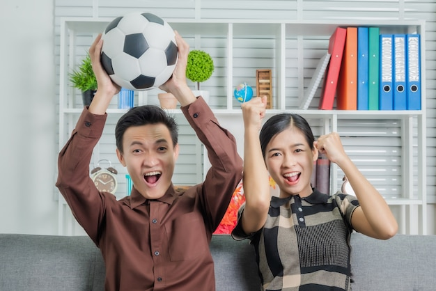 Good looking young asian couple looking surprised while sitting on sofa and watching soccer game on tv at home.