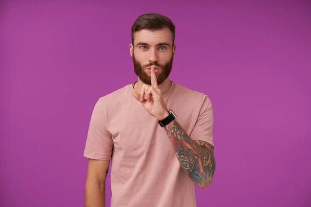 Good looking young bearded brunette man with tattooes keeping forefinger on lips in hush sign, asking to keep secret, wearing beige t-shirt and trendy accessories while posing on purple
