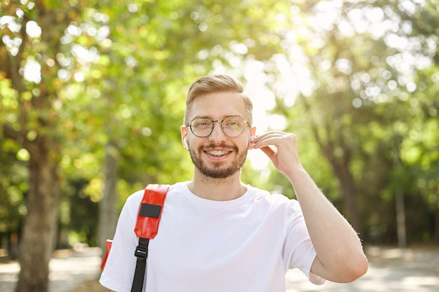 Good looking young bearded man looking with wide smile, wearing eyewear and headphones, being positive and cheerful, standing over green trees