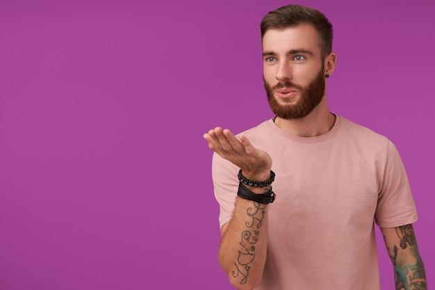 Симпатичный молодой бородатый татуированный мужчина с модной стрижкой, держащий поднятую ладонь и дующий воздушный поцелуй в сторону, флиртующий с девушкой, позирует на фиолетовом в повседневной футболке