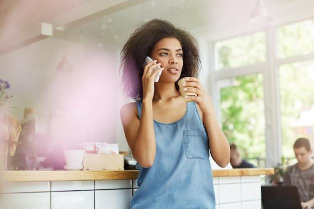 スマートフォンで話して、コーヒーショップに座って、エスプレッソを飲んで、心配そうな表情をよそ見カジュアルなスタイリッシュな服で黒い巻き毛の見栄えの良い若い黒肌アフリカ学生女性