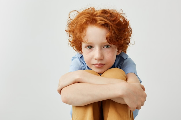 Good-looking young boy with curly red hair holding legs with hands, looking in aside with relaxed and calm expression.