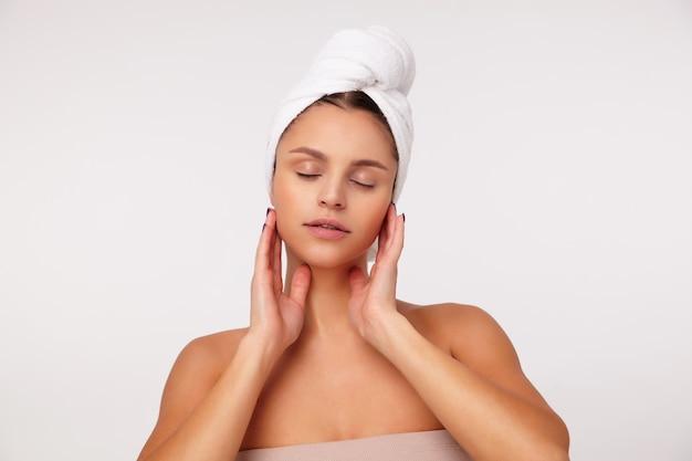 Красивая молодая брюнетка женщина держит глаза закрытыми, нежно касаясь лица поднятыми руками, делая косметические процедуры, стоя на белом фоне