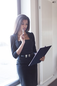 Good looking young business lady in black strong suite hold tablet