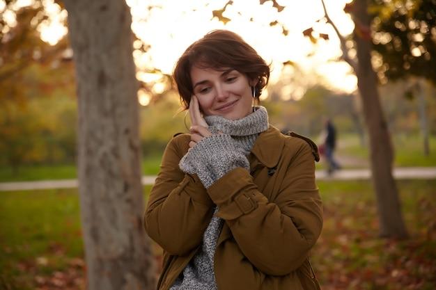 トレンディな暖かい服を着て、上げられた手で彼女の頬に触れ、都市公園を歩きながら心地よく笑っている格好良い若い魅力的な茶色の髪の女性