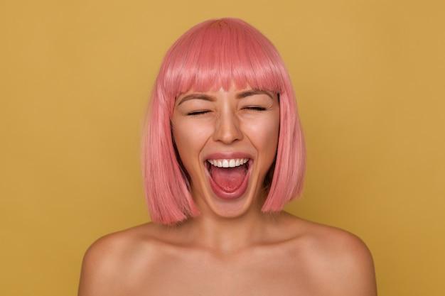 目を閉じてマスタードの背景の上に立っている間、彼女の口を大きく開いたままにしておくピンクのボブの髪型を持つ格好良い若い陽気な魅力的な女性