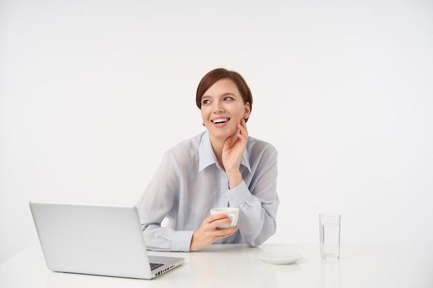 Bella giovane donna dai capelli castani allegra con taglio di capelli corto alla moda che tocca il collo con la mano alzata e sorride felice, posa su bianco con una tazza di tè