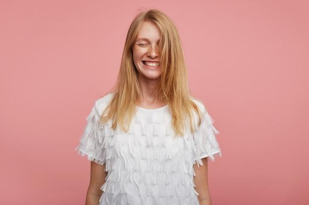 セクシーな服を着て、幸せそうに笑っている間、目を閉じて、ピンクの背景の上に手を下ろして立っている、セクシーな髪の格好良い若い陽気な女性