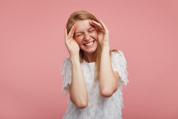 좋은 찾고 젊은 쾌활한 사랑스러운 빨간 머리 여자가 그녀의 얼굴에 손바닥을 들고 우아한 블라우스에 분홍색 배경에 서있는 닫힌 눈으로 행복하게 웃고