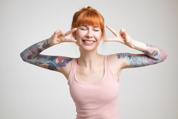 勝利の兆候で手を上げ、目を閉じて幸せに笑って、白い背景の上にポーズをとって、セクシーな髪の格好良い若い陽気な入れ墨の女性