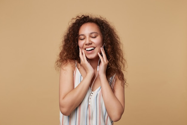 Bella giovane femmina bruna riccia sorridente volentieri durante l'ascolto di brani musicali e tenendo le mani alzate sul viso, isolato su beige