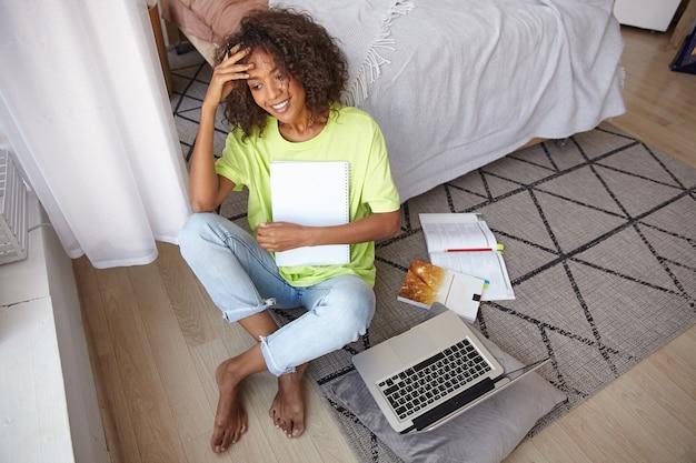 Красивая молодая кудрявая женщина с каштановыми вьющимися волосами сидит на ковре с геометрическим принтом, прерывает учебу и мечтательно смотрит в окно