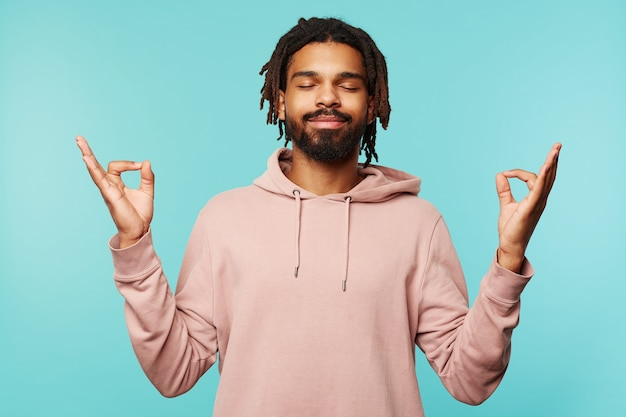 Good looking young dark skinned bearded guy with dreadlocks keeping his eyes closed while smiling pleasantly, posing over blue background with raised hands
