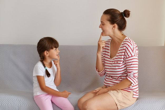 Good looking young european language therapist teaching small female child right sounds pronunciation, working on speech difficulties with little patient while sitting on comfortable sofa.