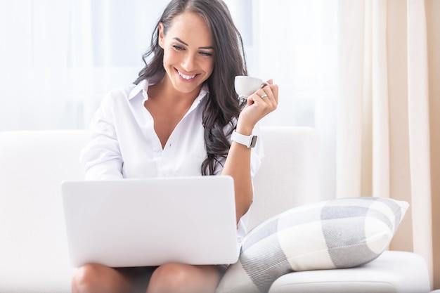 Симпатичная молодая женщина смеется в ноутбуке на коленях во время видеозвонка во время карантина и пьет кофе в руке в своем доме.